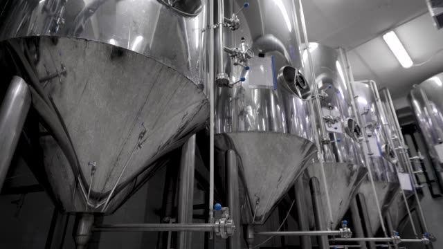 camera is moving along shine modern tank for mashing malt for brewing beer in brewery plant - acciaio inossidabile video stock e b–roll