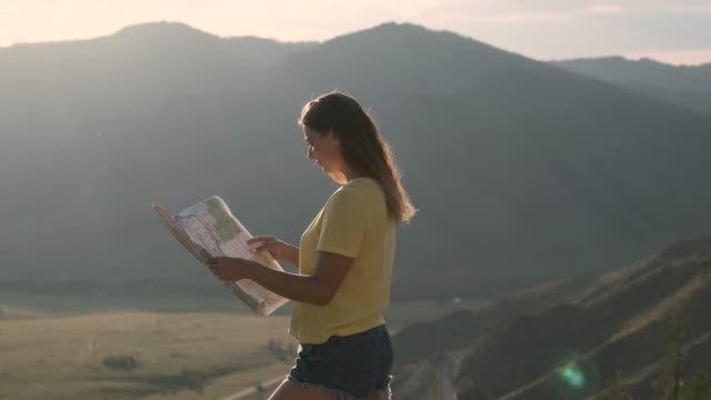 Camera movement around a tourist girl who stands on the edge of a cliff and holds a map in her hands Camera movement around a beautiful tourist girl who stands on the edge of a cliff and holds a map in her hands in the summer california map stock videos & royalty-free footage