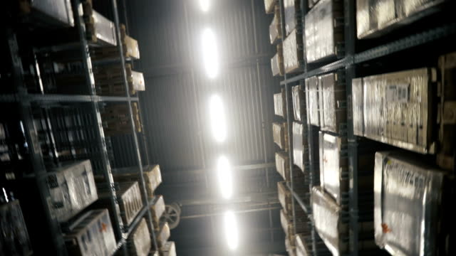 Camera moves between palettes with cardboard boxes and different materials in a storage warehouse. Dolly shoot video