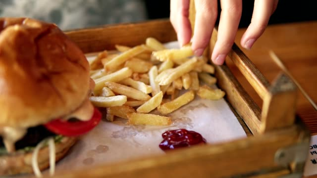 camera moves from female hands taking french fries and showing her smiling face while eating. slowmotion shot - junk food stock videos and b-roll footage