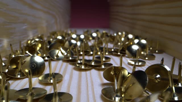 Camera moves over the scattered pushpins. Super macro shot of golden shiny office supplies that lie in a wooden box. Vertical slide back