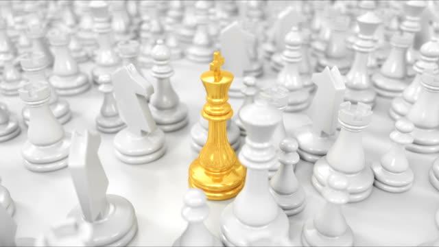 kamera bewegt sich über weiße schachfiguren und konzentriert sich auf den goldenen könig - könig schachfigur stock-videos und b-roll-filmmaterial