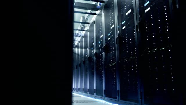 kamera bewegt sich durch big working data center mit server-racks und glaskabel. - netzwerkserver stock-videos und b-roll-filmmaterial