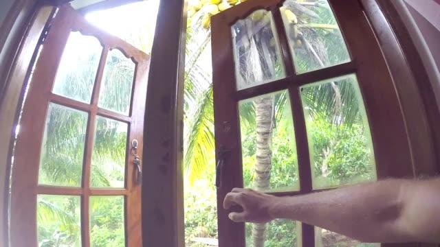 stockvideo's en b-roll-footage met pov camera beweegt richting in de palmbomen tuin venster geopend met mannenhand. leven in de exotische natuur concept video. - photography curtains