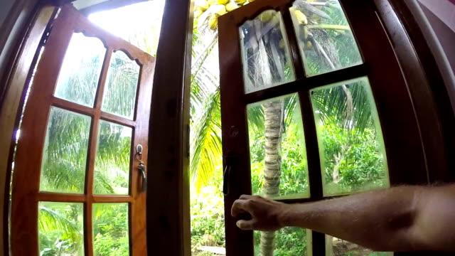 vídeos de stock e filmes b-roll de camera moves towards into the palm trees garden window opened with male hand. living in exotic nature concept pov video. - sri lanka