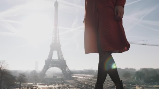 vidéos et rushes de la caméra se déplace de haut en bas sur la belle femme de sourire dans la robe rouge posant près du mouvement lent ensoleillé de panorama de tour eiffel. - mode paris