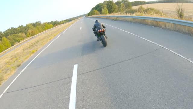高速道路で現代のスポーツバイクに乗ってバイカーの周りを移動するカメラ。モーターサイクリストは日没時に田舎道で彼のオートバイをレース。旅行中に自転車を運転する男。自由と冒険� - エクストリームスポーツ点の映像素材/bロール