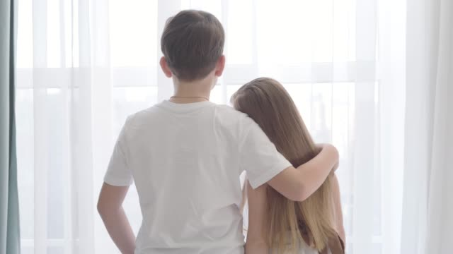 Camera moving away from Caucasian girl and boy standing together in front of the window. Girl's head is on boy's shoulder. First love, happiness. Camera moving away from Caucasian girl and boy standing together in front of the window. Girl's head is on boy's shoulder. First love, happiness. brown hair stock videos & royalty-free footage