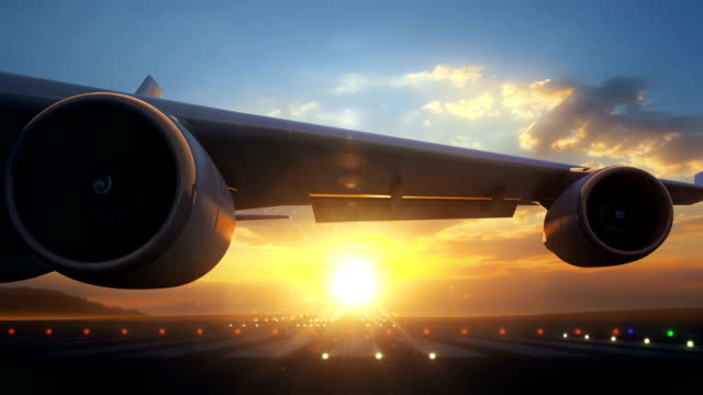 Camera moving close to airplane wing showing its engines rotating Camera moving close to airplane wing showing its engines rotating. The airplane is on runway and ready to start taking off procedure. Beautiful sunset seen behind the airplane. airport runway stock videos & royalty-free footage