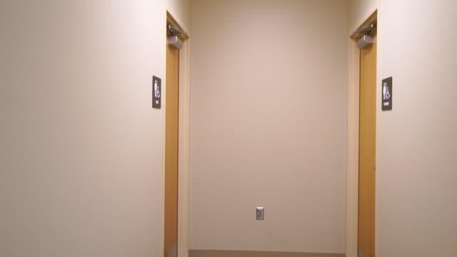 Camera moving down hallway towards Men's Bathroom Sign video