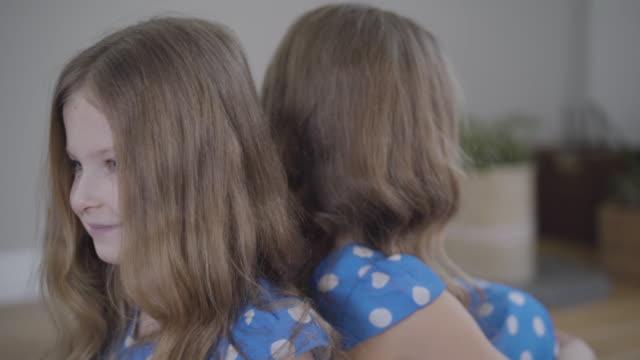 kamera bewegt sich von links nach rechts um zwei identische zwillingsschwestern in ähnlichen blau gepunkteten kleidern. brünette schwestern mit grauen augen posieren drinnen am wochenende. einheit, glück, lebensstil. - rücken an rücken stock-videos und b-roll-filmmaterial