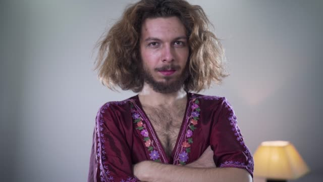 Camera moving from left to right around young bearded Caucasian man with long curly hair and brown eyes looking at camera and smiling. Portrait of positive intersex person standing with hands crossed. Camera moving from left to right around young bearded Caucasian man with long curly hair and brown eyes looking at camera and smiling. Portrait of positive intersex person standing with hands crossed. long hair stock videos & royalty-free footage