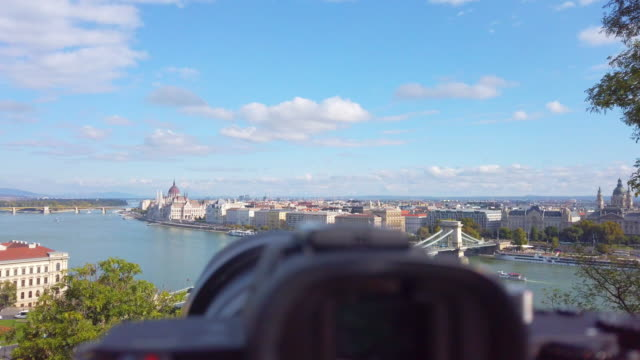 Camera on tripod taking time lapse of Danube river and Chain Bridge in morning in Budapest in Hungary
