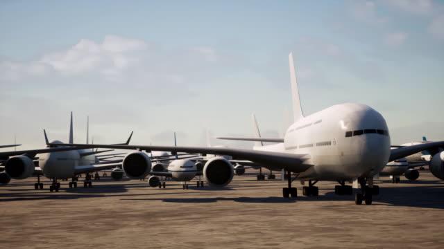 kamera schwenkt über zahlreiche flugzeuge, die aufgrund einer globalen pandemie auf einer start- und landebahn des flughafens gelandet sind - asphalt stock-videos und b-roll-filmmaterial