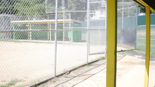 vídeos y material grabado en eventos de stock de cacerolas de la cámara a través de caseta vacía de pequeña liga béisbol - sófbol