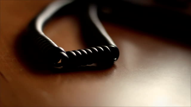 Camera pans by old telephone cord from landline phone video