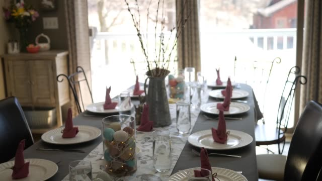 camera pans down decorative dining room table set for an easter dinner - jesus christ filmów i materiałów b-roll