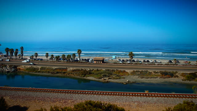 Camera pans left to right showcasing the famous surf spot, Cardiff Reef in San Diego, California as waves break and surfers surf. video