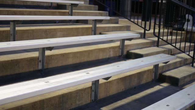 camera pans over empty bleachers at a sporting event at night - stand video stock e b–roll