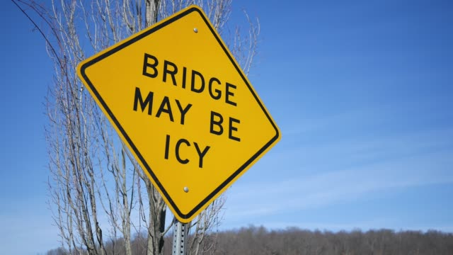Camera pans to a bridge may be icy sign in winter in North America afternoon - vídeo