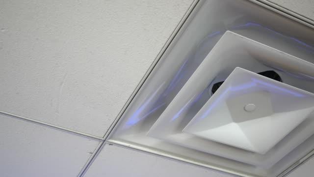 空気オフィスの天井の通気口カバーにカメラのパン - エアコン点の映像素材/bロール