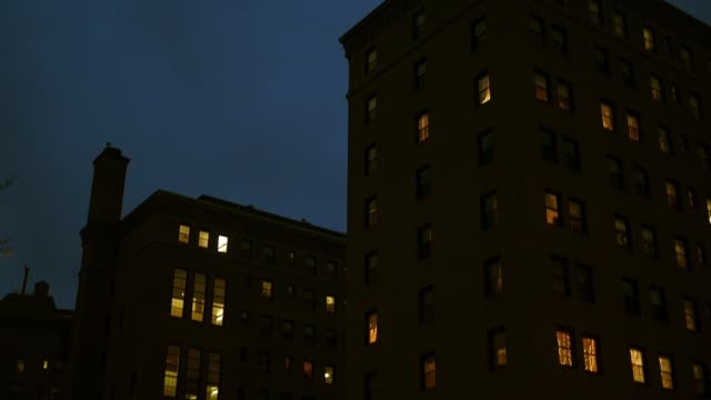 Camera pans up a a brick apartment building in the city at night - vídeo