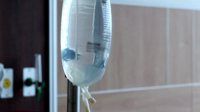 Camera pans up IV Tube to IV Bag in hospital room video