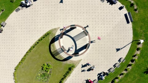 stockvideo's en b-roll-footage met camera stijgt over ronde schommels in groen park op zonnige dag - cirkel
