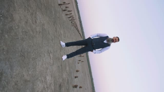 360 camera roll effect. Handsome bearded mature man in suit posing outdoors on beach during sunset, slow motion video
