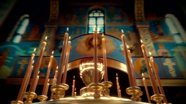 camera rotation around candle on candlestick holder in church - candeliere video stock e b–roll