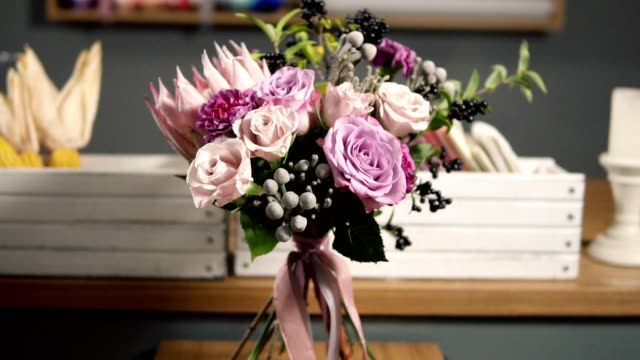 Camera round movement: beautiful fresh bouquet in the flower shop: floral composition consists of Rose, Brunia, Protea with beautiful ribbon video