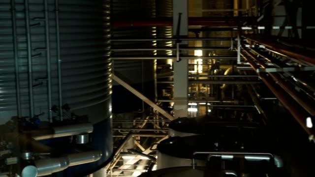 stockvideo's en b-roll-footage met camera toont buizen die leiden tot enorme reservoirs bij brouwerij - lood