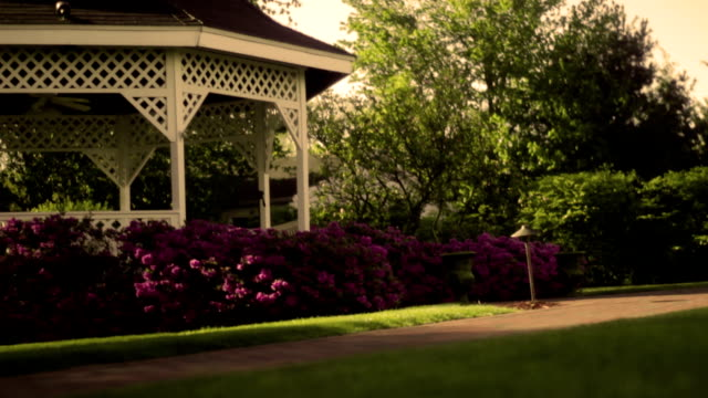 camera slides past pavilion in beautiful gardens at sunset - joseph kelly stock videos and b-roll footage