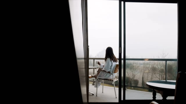 camera slides right revealing beautiful woman in gown having coffee at room terrace with foggy autumn view slow motion. - terrazza video stock e b–roll