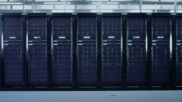 camera slide-trough shot of a working data center with rows of rack servers. led lights blinking and computers are working. - rozwiązanie filmów i materiałów b-roll