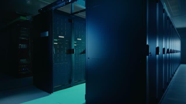 行とラック マウント型サーバの作業データ センターのカメラ スライド トラフ ショット。led ライトが点滅しているとコンピューターが働いています。周囲の光が暗い。 - スーパーコンピューター点の映像素材/bロール