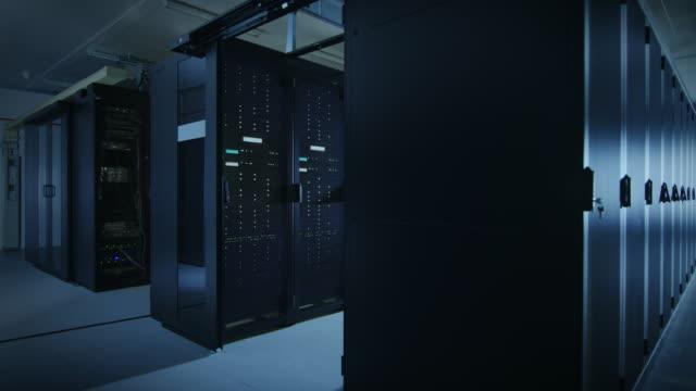 行とラック マウント型サーバの作業データ センターのカメラ スライド トラフ ショット。led ライトが点滅しているとコンピューターが働いています。周囲の光が暗い。緑のシェーディング� - スーパーコンピューター点の映像素材/bロール