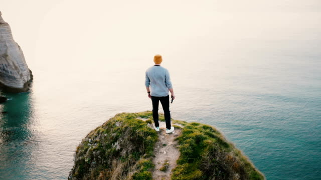 camera spins around young happy caucasian man standing at epic sunset ocean view on top of normandy rocky shore cliff. - indywidualność filmów i materiałów b-roll