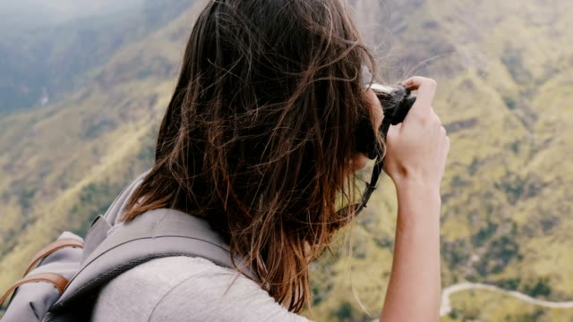 Camera tilts up on young female tourist with backpack and camera taking photos of amazing mountains on Sri Lanka travel. video