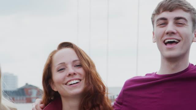 vidéos et rushes de la caméra suit à travers des visages du groupe des amis masculins et féminins d'étudiant d'université restant sur le pont dans le cadre urbain ensemble - tiré au mouvement lent - 18 19 ans