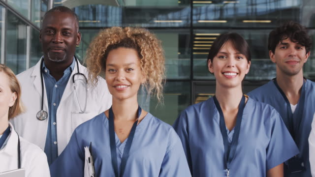 Camera tracks across faces of male and female medical team standing in modern hospital building - shot in slow motion Portrait Of Medical Team Standing In Modern Hospital Building group of people stock videos & royalty-free footage