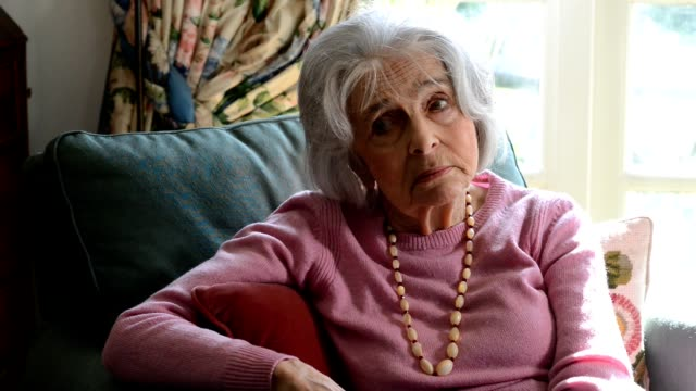 Camera tracks across frame as sad looking senior woman sits in armchair at home Lonely Senior Woman Sitting In Armchair At Home lounge chair stock videos & royalty-free footage