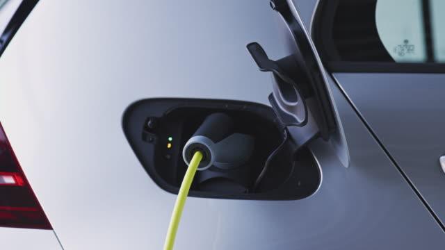 la telecamera traccia lungo il lato dell'auto elettrica in garage e si ferma sul cavo di ricarica collegato al veicolo - girato al rallentatore - carica elettricità video stock e b–roll