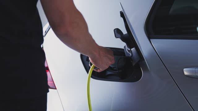 la telecamera traccia lungo il lato dell'auto elettrica in garage mentre l'uomo attacca il cavo di ricarica al veicolo - girato al rallentatore - carica elettricità video stock e b–roll