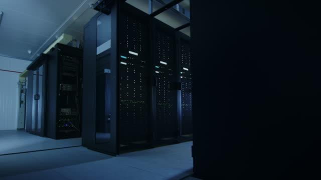 行とラック マウント型サーバの作業データ センターのカメラ チュートリアル ショット。led ライトが点滅しているとコンピューターが働いています。 - スーパーコンピューター点の映像素材/bロール