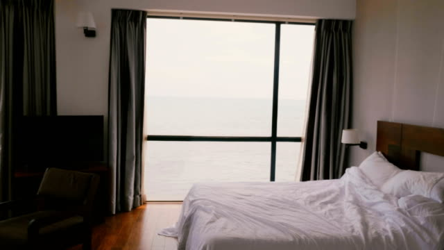 Camera zooms in on large modern comfortable hotel apartment window with incredible scenic cloudy ocean waves view.