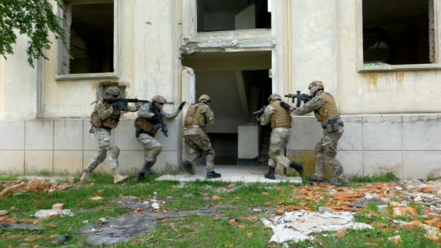 Camouflaged soldiers walking in an abandoned building with weapons during an operational exercise video