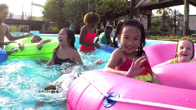 Camp counselors, children at water park on lazy river A multi-ethnic group of children at a water park with two camp counselors on inflatable rings float down the lazy river, splashing the camera and looking into the lens. pool party stock videos & royalty-free footage