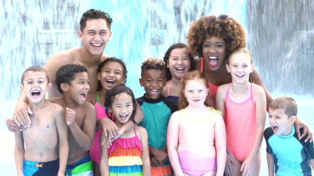 Camp counselors with multi-ethnic children at water park video