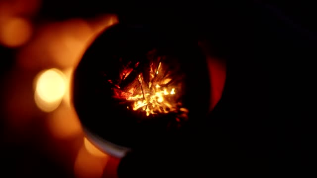 Camp fire reflecting in glass ball. Sunset